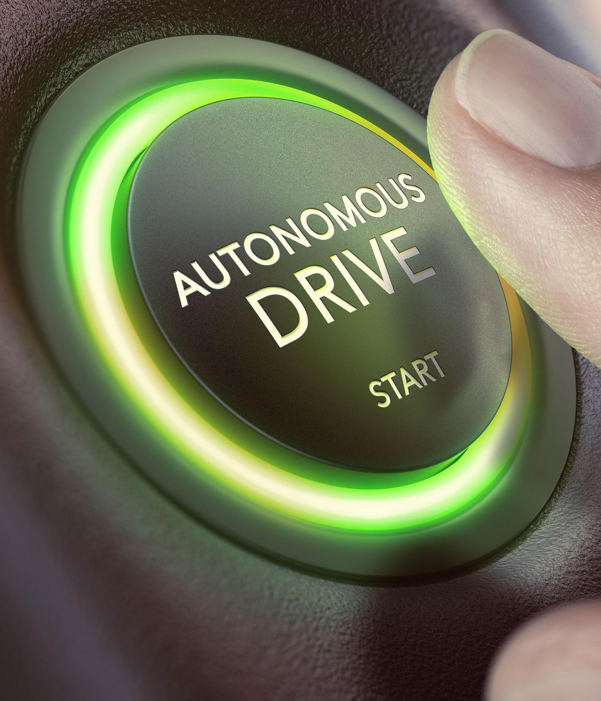 """Ein Finger drückt einen Knopf auf dem """"Autonomous Drive Start"""" steht."""